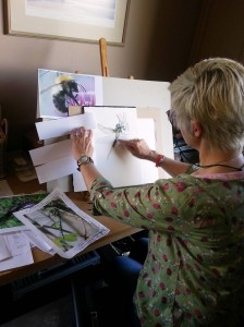 Cath, painting a dragonfly at her easel